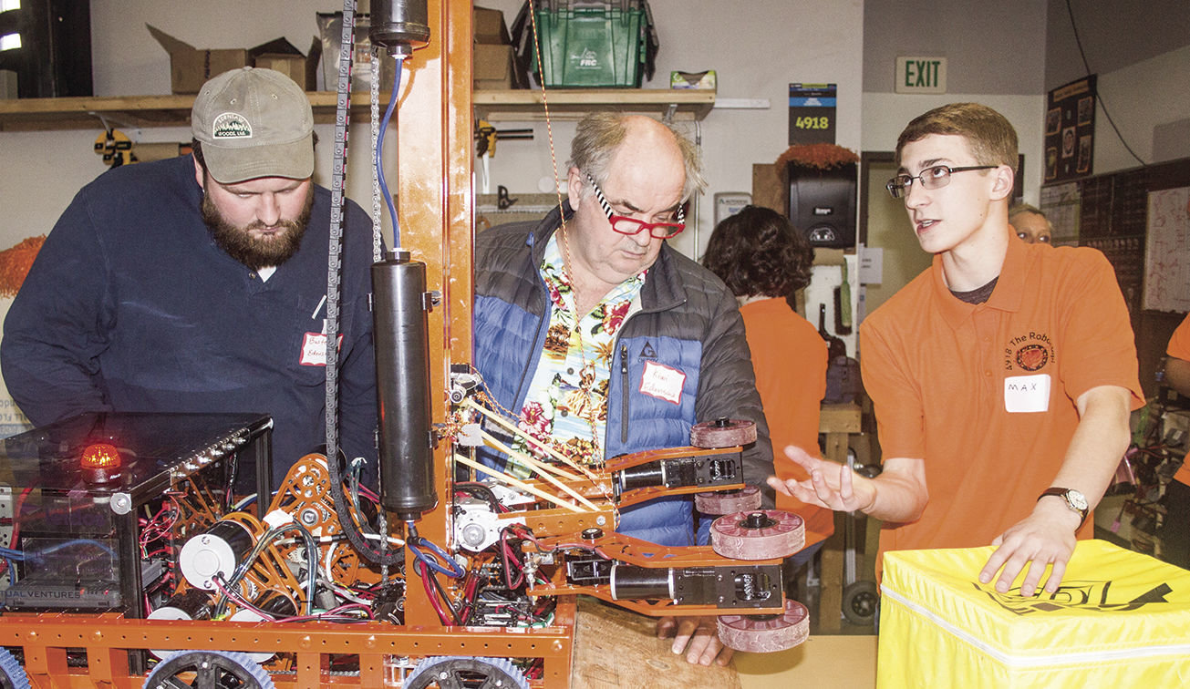 Edensaw Woods' Buster Ferris, far left, and Kiwi Ferris, center, examine the Port Townsend Roboctopi's competition robot, as team captain and president Max Morningstar explains its inner workings. Photo by Kirk Boxleitner