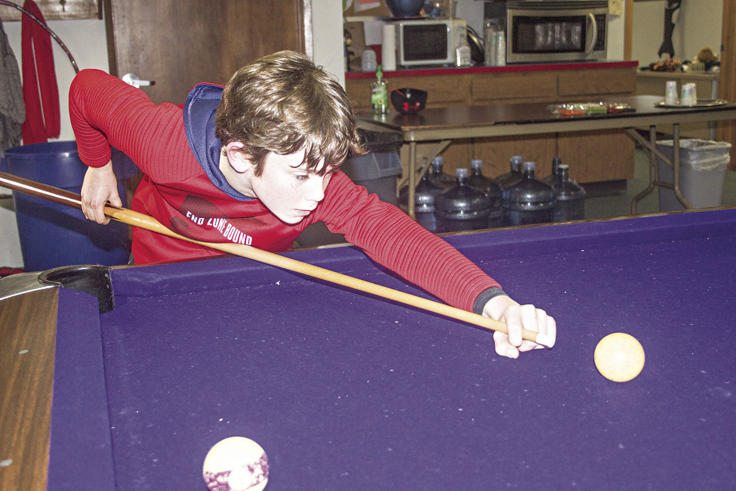 William Moseley takes aim at a pool table at the Jefferson Teen Center. Photos by Kirk Boxleitner