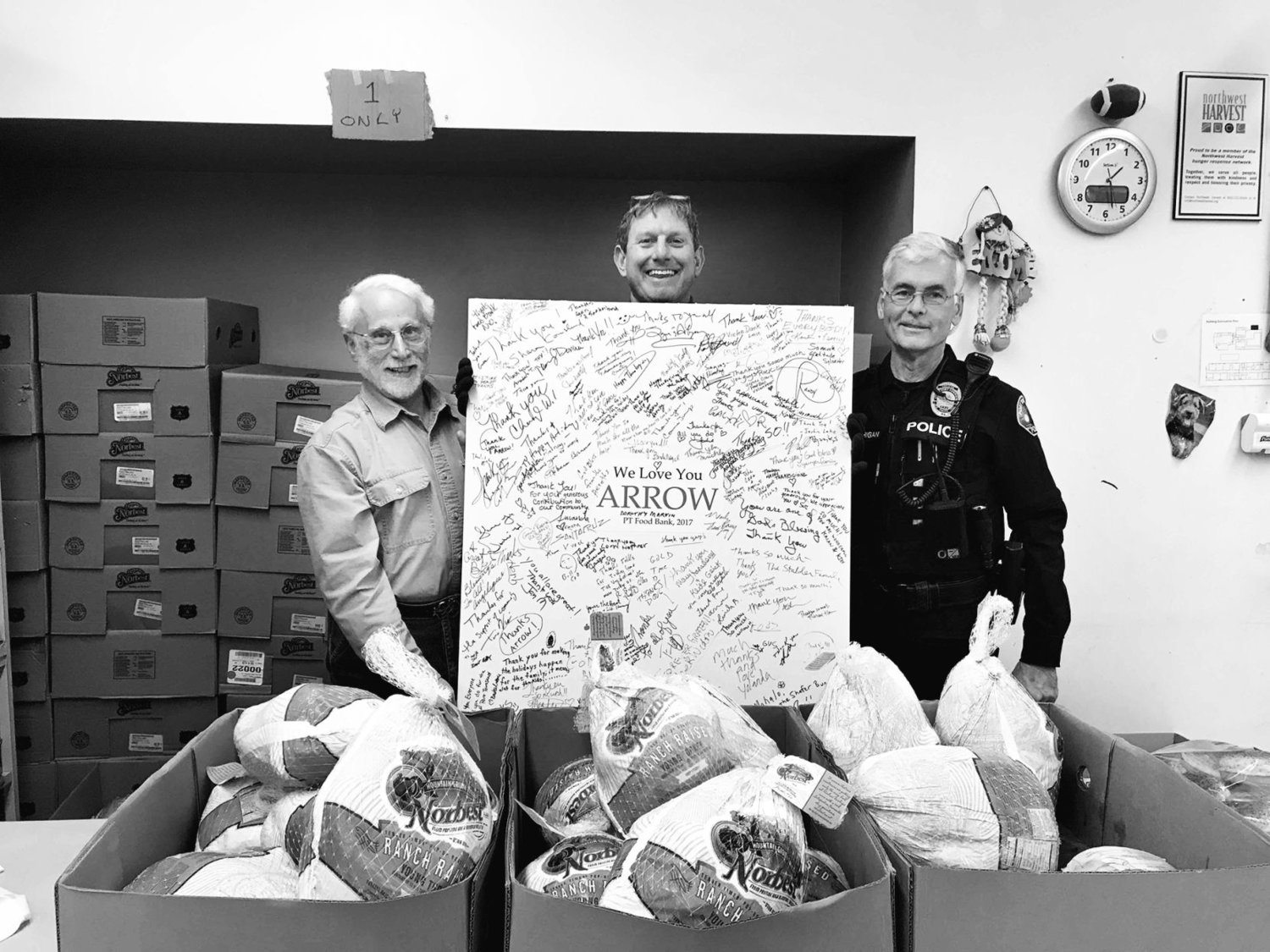 Earll Murman, Arran Stark and Port Townsend police Officer Bill Corrigan stand behind artwork thanking Arrow Lumber for donating turkeys for eight years in a row. Photo courtesy Earll M. Murman