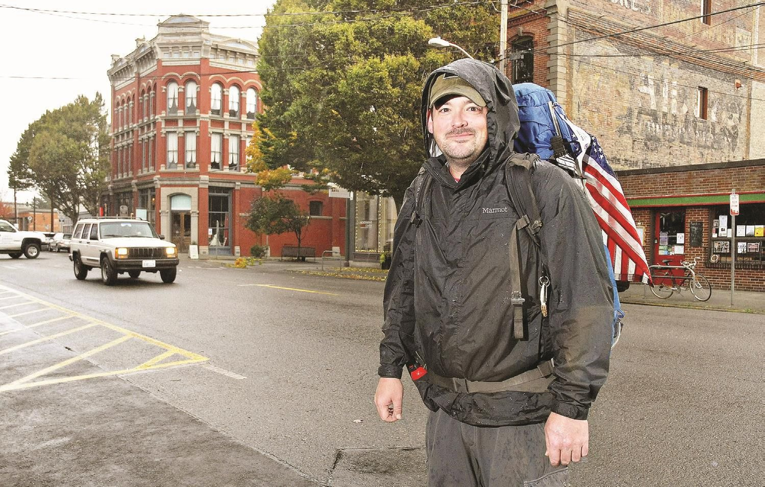 Eli Smith, who is hiking to all four corners of the U.S., stands in downtown Port Townsend with his 60-pound backpack and U.S. flag Oct. 18.