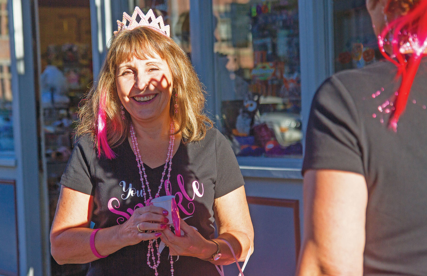 A sparkling tiara worn by a Blue Heron Middle School staff member creates a shadow on school employee Sandi Reid's face. A group of Blue Heron women wore T-shirts they had made and pink accessories during Girls' Night Out.