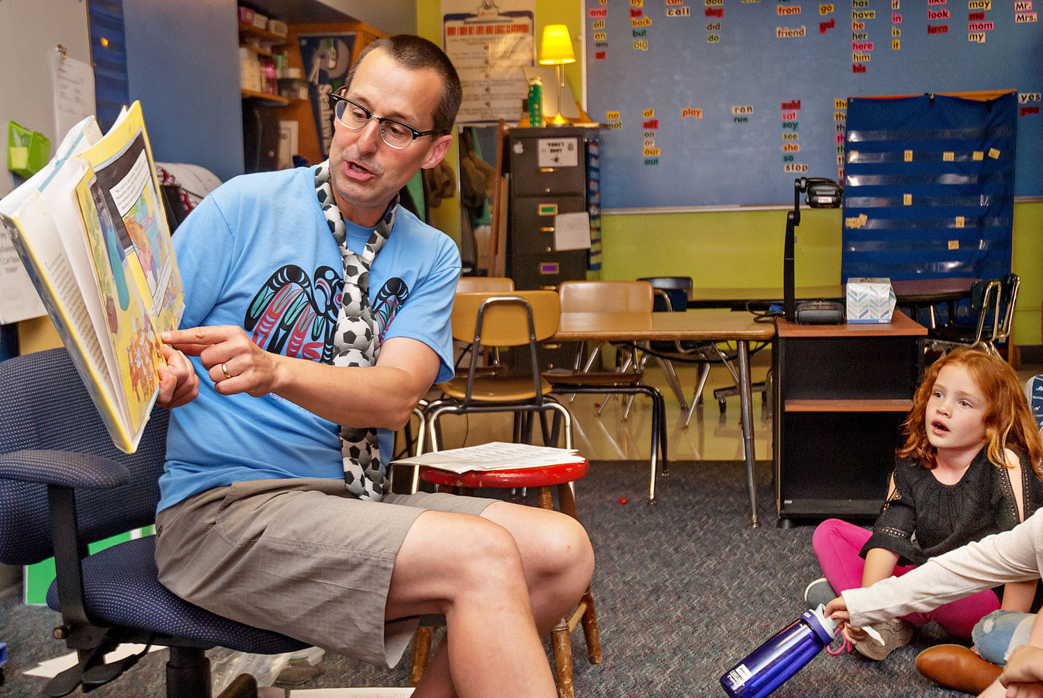 Grant Street Elementary School second-grade teacher Peter Braden enthusiastically reads from a book during the first day of school Sept. 5 as student Hope Quinn, 7, of Port Townsend, listens. Quinn is the daughter of Ashley Quinn. Photo by Chris Tucker