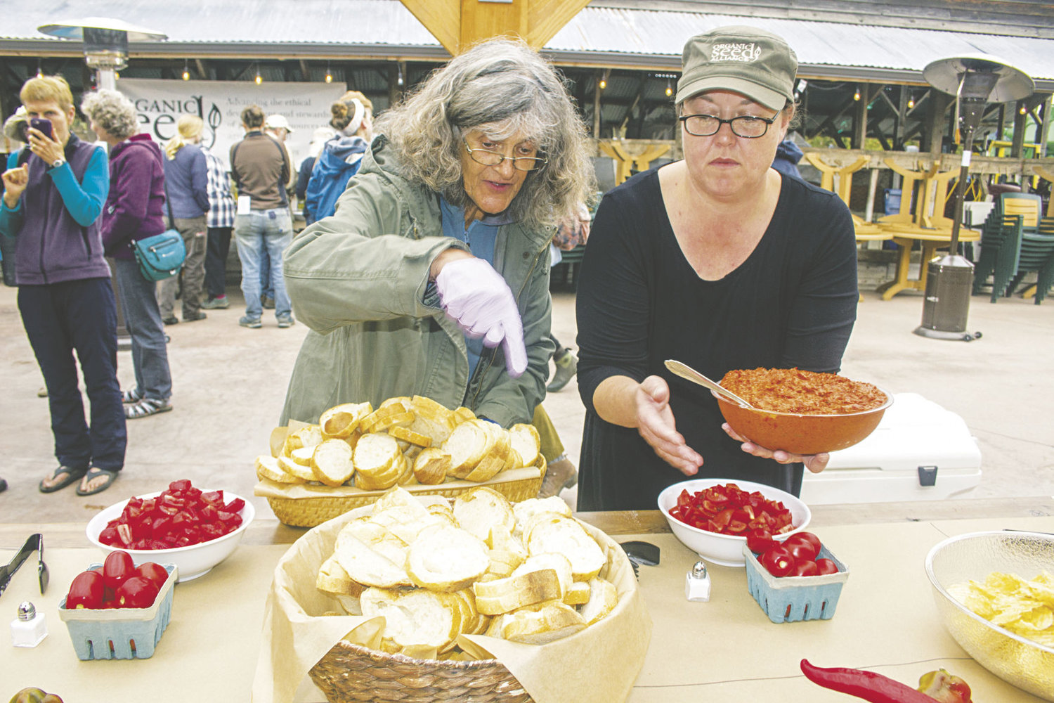 Eve Dixon (left) and Kiersten Boulter set out bowls of bread and red pepper tapenade, prepared on site at Finnriver Farm.