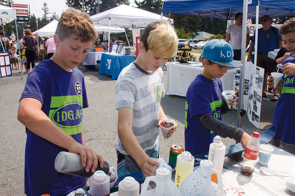 (From left) Leland Anderson, Makai Ward and Cooper Anderson cool down with Bill's Snow Cones, served from his customized Volkswagen.