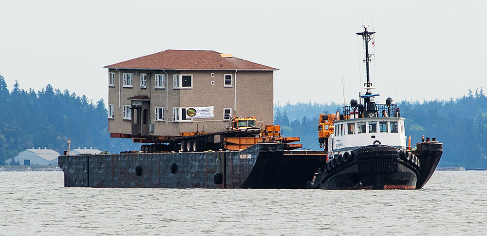 The fourplex and a truck sit atop a Harken barge floating off the Port Townsend waterfront on May 10. The tug D.D. Catherwood towed the barge. Photo by Chris Tucker