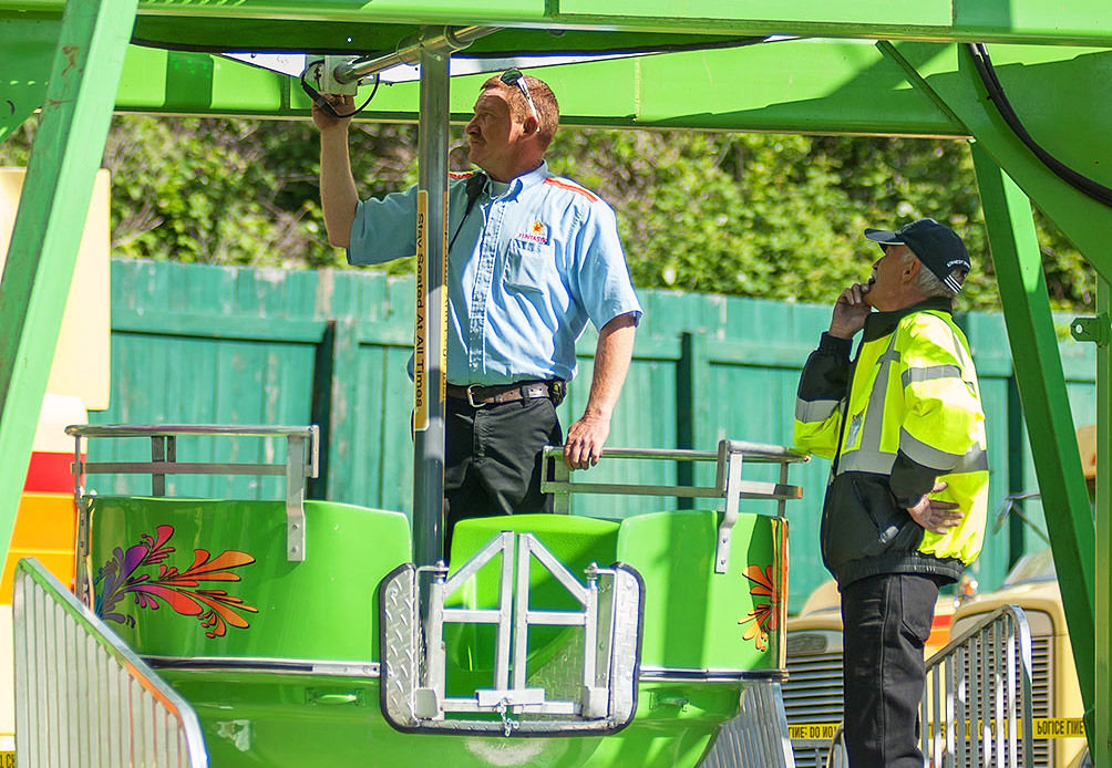 Funtastic Carnival manager Keith Ellefson (left) looks over the Ferris wheel with Richard Spromberg, a state-certified ride inspector, at Memorial Field Friday morning, May 19 after three people fell out of the ride around 5:45 p.m. Thursday night. Photo by Chris Tucker