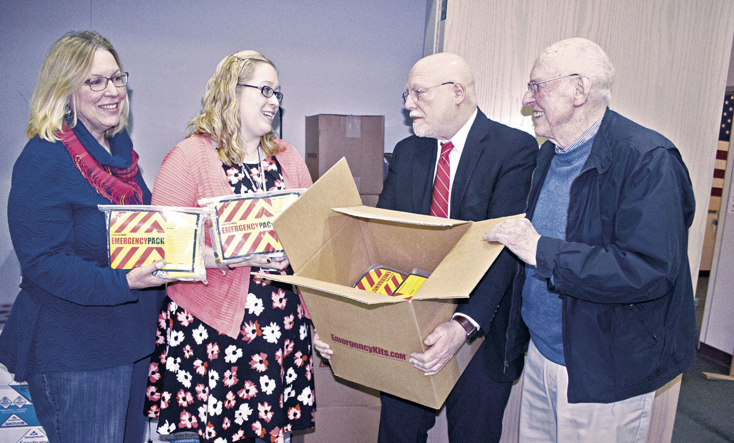 Jane Lohry Armstrong (far left) and Kalie Enlow, principal of Chimacum Creek Primary School in Port Hadlock, check in the emergency kits handed off to the school by Ron McClung, pastor of the Peace Lutheran Fellowship, and Z. Jack Randall (far right). Photo by Kirk Boxleitner