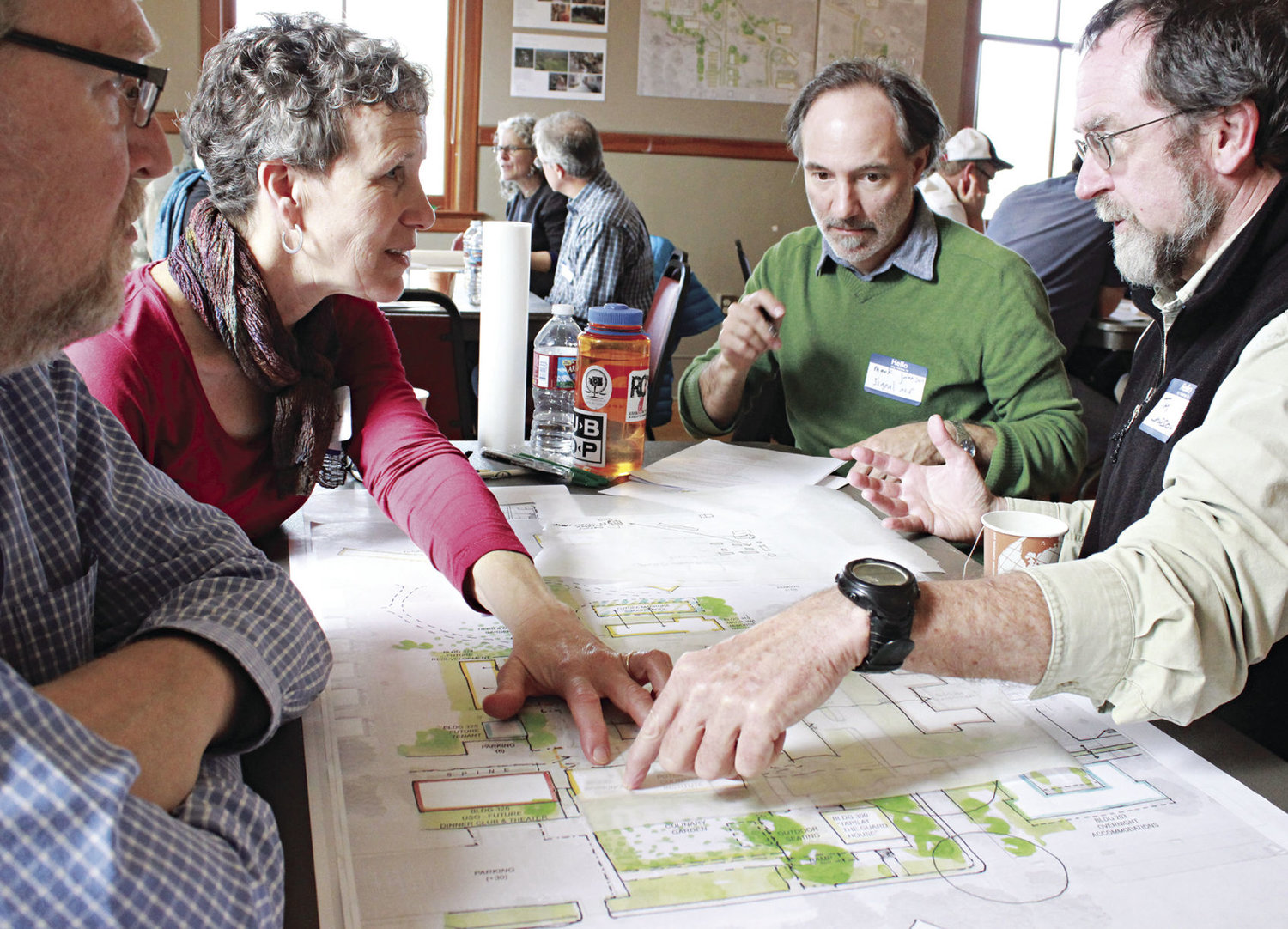 Plans for the Makers Square at Fort Worden State Park are now in progress, and are inspected by (from left) consultant Kris Tucker, architect Mark Johnson and Tim Lawson of the woodworking school. Photo by Charlie Bermant