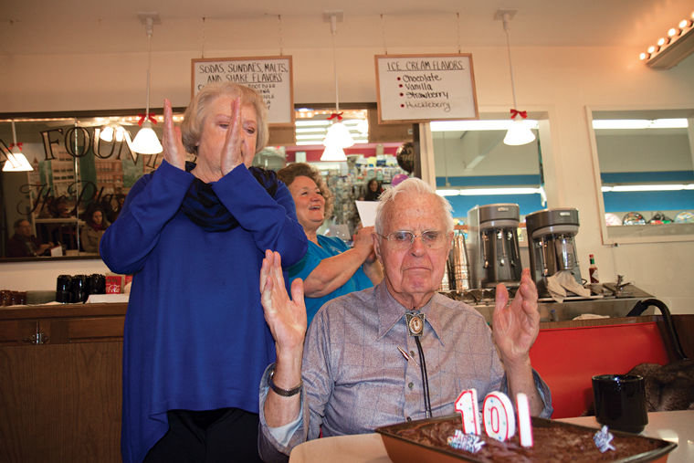 "Richard ""Dick"" Konizeski (seated) claps after blowing out candles on a cake during a celebration of his 100th birthday at Don's Soda Fountain on Thursday, March 9. Behind him are friend Barbara Blowers (left) and Sam Johnson of the fountain (right). Photo by Patrick Sullivan"