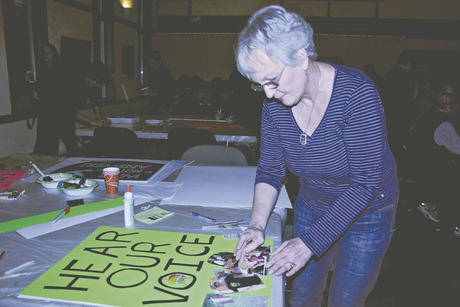 Sue Edwards puts the finishing touches on her poster at the Quimper Unitarian Universalist Fellowship Jan. 16. Photo by Kirk Boxleitner