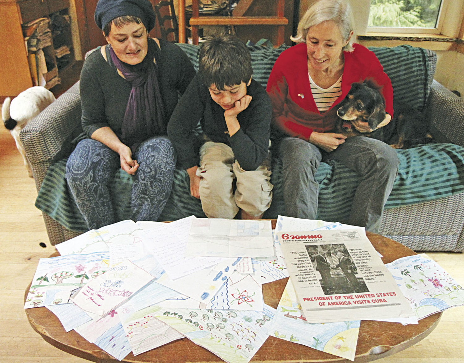 Lorena Murray (left) and her son, Diego Garcia, with Chimacum neighbor Heather Harding look over artwork that has been sent to Garcia thanks to Harding, a travel guide. Murray and Harding help translate the letters from Spanish for Garcia. Photo by Allison Arthur
