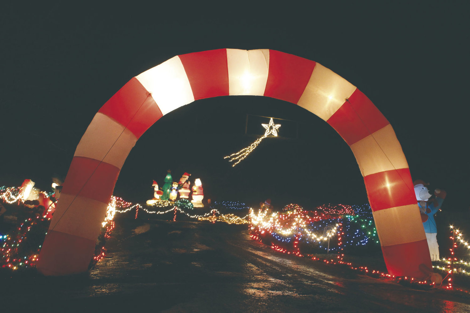 A candy cane arch guides visitors to a circular driveway at the Hoffman family's display on Leland Valley Road West, just off U.S. Highway 101 near Leland Cutoff Road. People may drive by on Leland Valley Road West (there is room to turn around), and/or turn under the candy cane arch to access the circular driveway. It's OK to get out and walk around; just be aware the inflatables are secured with numerous tie-downs. Photo by Patrick Sullivan