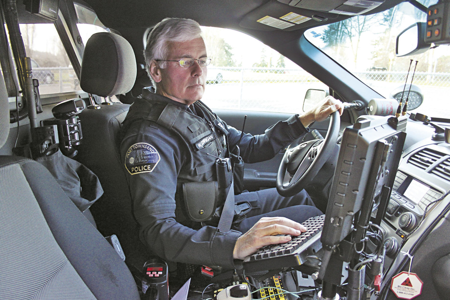 "Officer Bill Corrigan, well known as a Port Townsend Police Department traffic enforcement officer, parks his patrol vehicle to check his computer. ""The number-one cause of vehicle collisions in Port Townsend is following too closely,"" he said. Photo by Kirk Boxleitner"