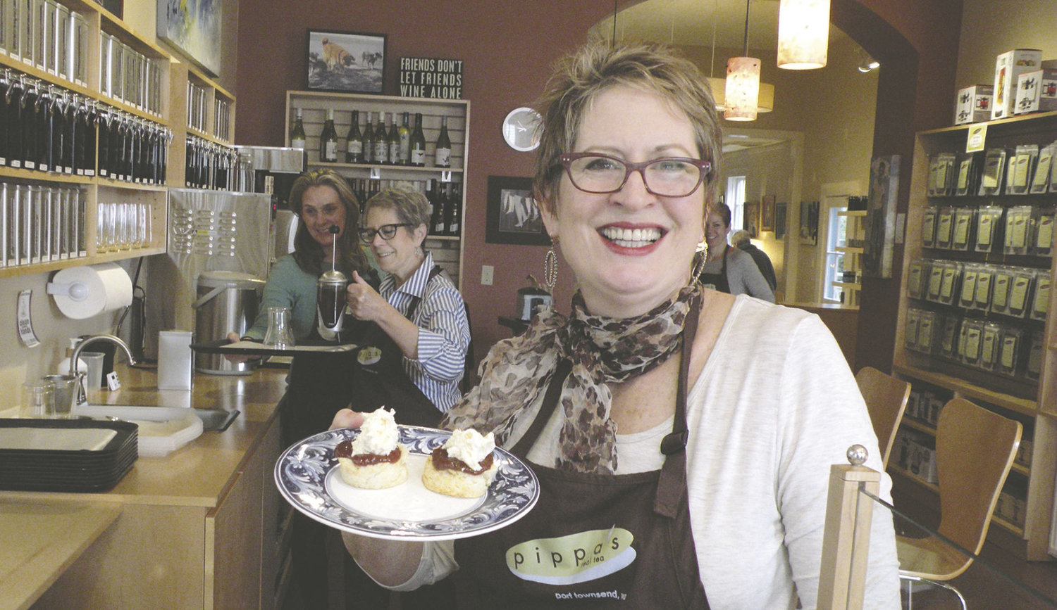 "Pippa Mills, owner of Pippa's Real Tea in downtown Port Townsend, holds some of her scones and clotted cream as Julie Marquez and Jill Hamilton, ""tea mavens,"" work on a pot of tea for a customer. The business has been named Best Tea House in the Seattle area by Seattle A-List for 2016. Photo by Allison Arthur"