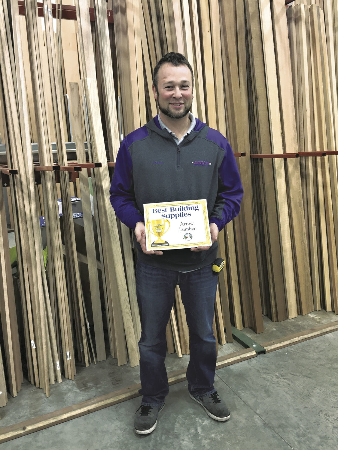 Cadian Hendricks of Arrow Lumber accepts the award for the company as the Reader's Choice best place to go for building supplies in Jefferson County.