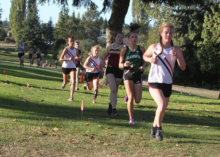 "Competing Sept. 28 on Port Townsend's ""home"" cross-country course are (wearing white) Rachel Matthes (background), Anika Avelino, Ally Bradley and Aliyah Parson. Photo by Patrick Sullivan"