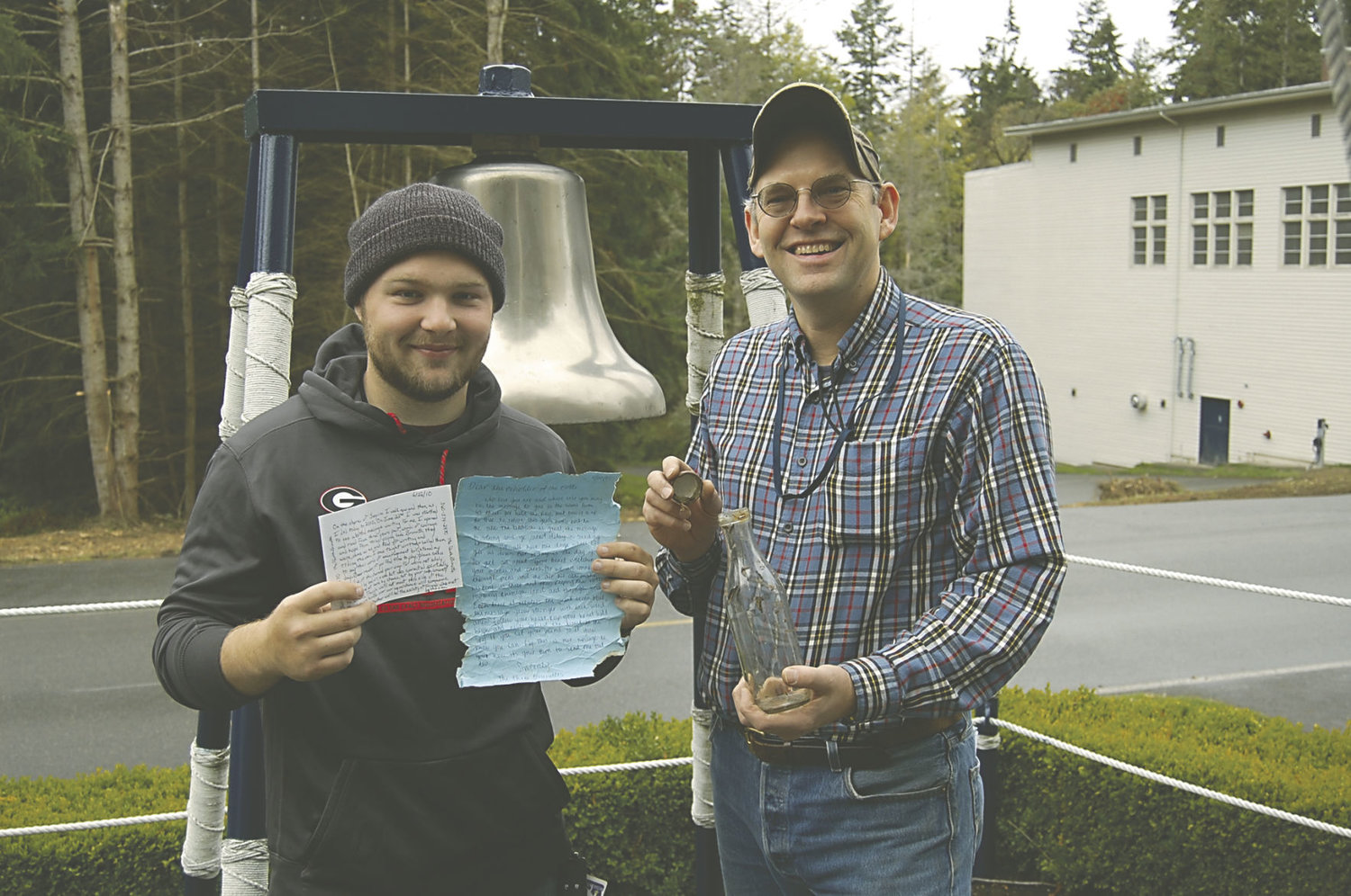 "A classic ""message in a bottle"" was located Oct. 13 along the shore of Indian Island on Port Townsend Bay. The bottle and note are displayed by Ben Carlson (left), Naval Facilities Engineering Command archaeological assistant, and Dave Grant, NAVFAC archaeologist. U.S. Navy photo by Phillip Guerrero"