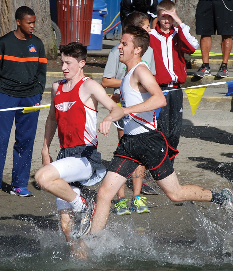 Port Townsend cross-country team senior Brennan LaBrie (right) races Lewi Hagos of King's through the water at the Tahoma Coed Relays at Lake Wilderness State Park in Maple Valley on Sept. 10, 2016. Courtesy photo by Janeen Armstrong
