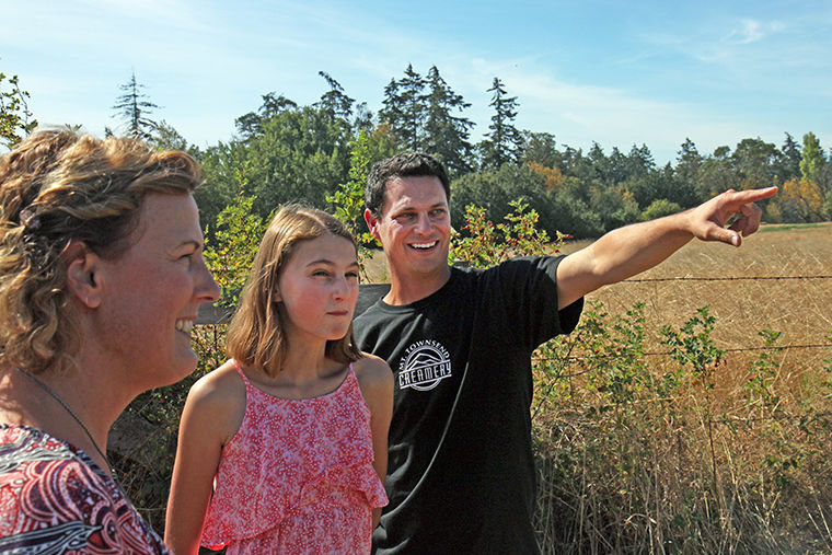 Ryan Trail, cofounder and CEO of Mt. Townsend Creamery, on Aug. 26 shows daughter Morgan, 12, and wife Pam the land along Howard Street on which the company plans to expand its capacity to produce cheese. Photo by Nicholas Johnson