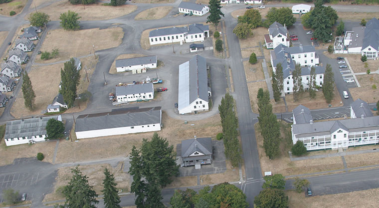"The Fort Worden Public Development Authority proposes to create the ""Makers Square"" complex, centered on Building 305 (center), the long, narrow building located behind the Guardhouse. To date, the PDA has raised $4 million to help with renovation of 10 underutilized buildings. 2012 Leader file photo by Patrick Sullivan, flight by Wyvern Air"