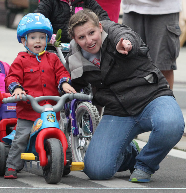 Nettie (Witheridge) Hawkins points son Parker Hawkins, age 2 and a half, to the people waiting at the Rhody Fest Trike Race finish line.