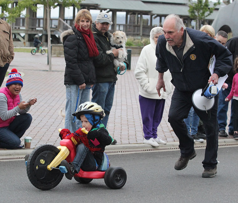 Dick Shipman of the Port Townsend Sunrise Rotary Club, Trike Race announcer, runs onto the course to give a push to Michael Babb, 3, who had been spinning his Big Wheel tire.