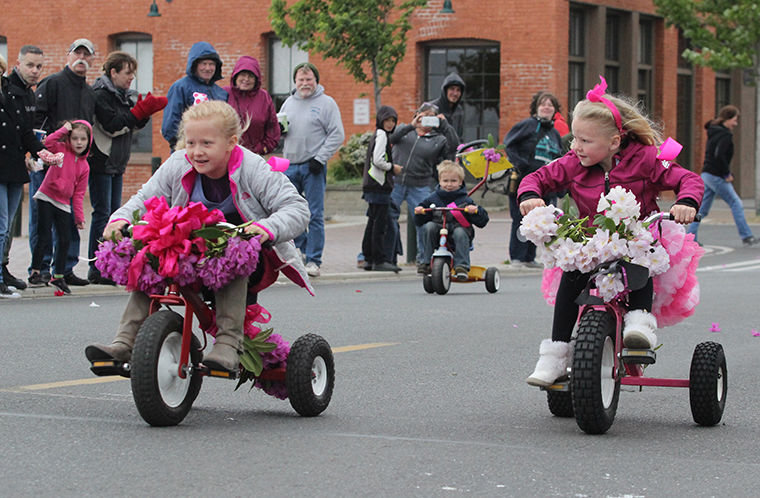 Breanne Huntingford (left) and Makena Slimp lead the 6-year-old contingent at the 81st Rhododendron Festival's Trike Race Wednesday evening. Slimp wins the race by a spoke, and also is judged by Rhody Royalty to have the Best Decorated entry.