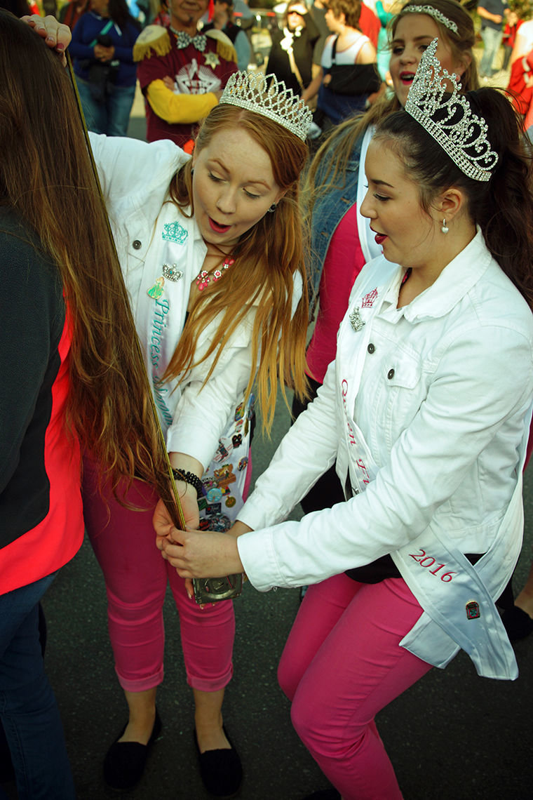 Rhody Fest Princess Morgan Wilford and Queen Fiona Shaffer use a tape measure to determine the length of a contestant's hair.