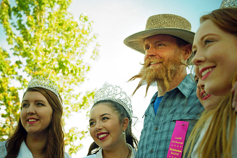 Michael Sharp poses for photos with Rhododendron Festival Royalty on Friday during the Rhody Festival Hair and Beard Contest.