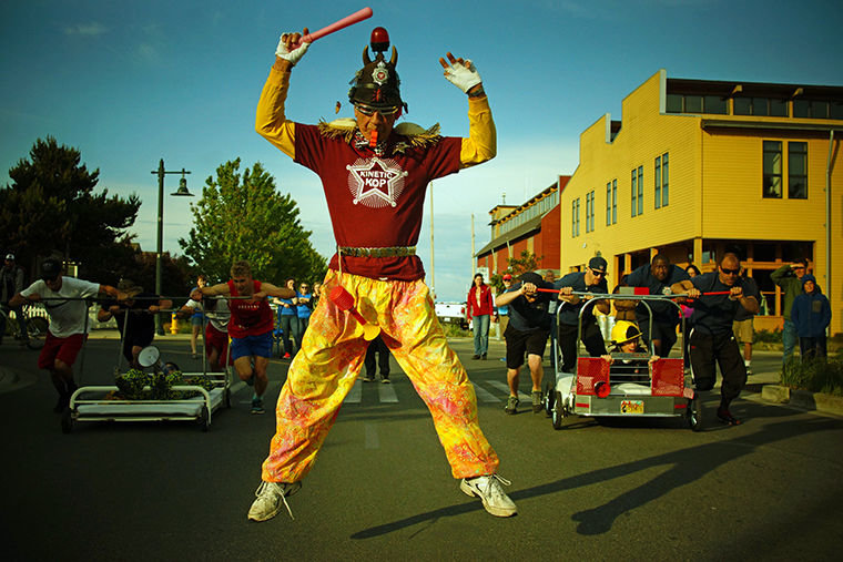 Kinetic kop John Lizwacko leaps into the air while blowing his whistle, signaling the start of a bed race between East Jefferson Fire Rescue and Port Townsend High School Youth Entertainment Coalition bed race teams. Photo by Nicholas Johnson