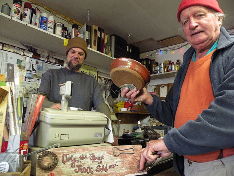 "Caleb Needham, shopkeeper at Waste Not, Want Not in Port Townsend, smiles when frequent shopper Francis Brophy points to a sign below the cash register that reads ""Only the Finest Junk Sold Here!"" Brophy picked up two bowls last Thursday. Photo by Allison Arthur"