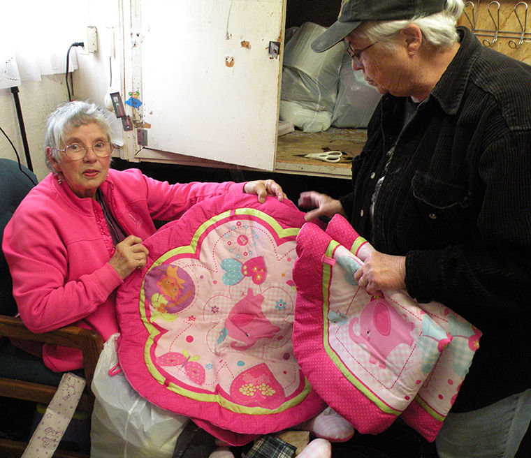 "Sarah Klause (seated, left) has been helping sort donations at the Adventist Thrift Shop in Port Townsend's Uptown District since 1999. She says that a lot of wonderful items, like the pink baby mats above, are donated. Manager Fran Carey (right) says the store, open from 10 a.m. to 3 p.m., Tuesday and Thursday only, typically sees 60 customers a day. The store used to be known as the ""Free Store,"" but it now has a price list. T-shirts cost 50 cents. People in need can get vouchers from Olympic Community Action Programs (OlyCAP) and use them like money, Carey says. Donations are accepted 24/7 these days. Photo by Allison Arthur"