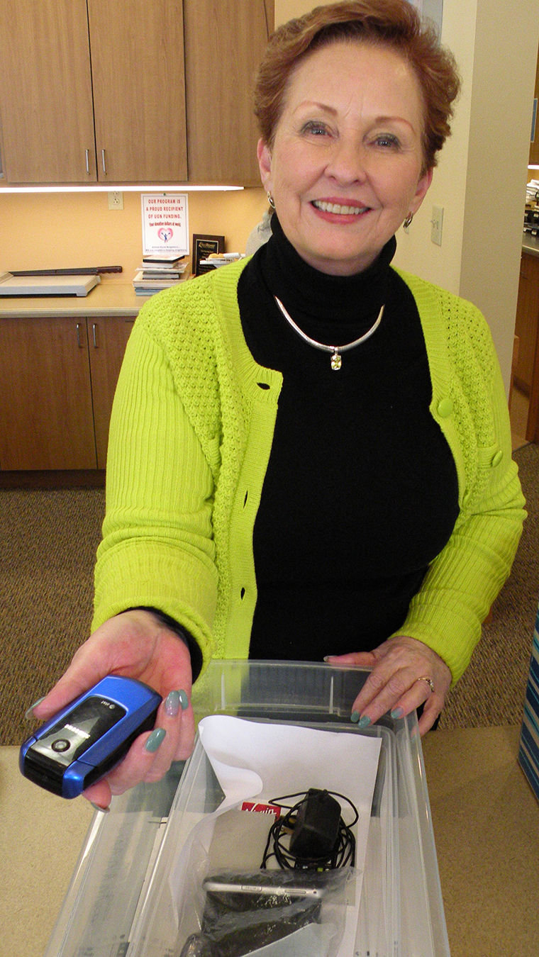 Dee Dee Spann, director of programs and services at Dove House Advocacy Services in Port Townsend, accepts a cell phone. The program recycles old cell phones and can exchange them for working cell phones for victims of domestic violence. Photo by Allison Arthur
