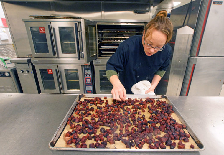 "Stacey Larsen, Port Townsend School District's director of food service, checks on a tray of roasted beets Tuesday morning, Nov. 24, ahead of that day's Thanksgiving feast lunch. The beets, which came from Dharma Ridge Farm in Chimacum, were originally intended for teachers and staff only, but Larsen made too many and decided the students might like some, too. ""They're like candy,"" she said upon tasting one. ""I think the kids will like these as much as the teachers."" Photo by Nicholas Johnson"