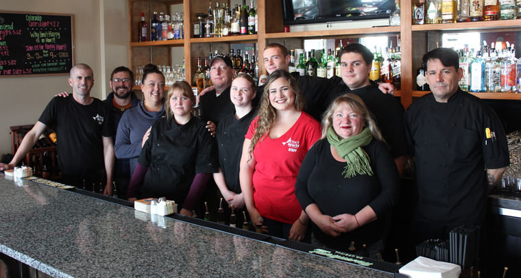 Doc's Marina Grill employees (from left) Colin Darlington, David Lindsay, manager Teresa Schultz, Emily Smith, Kevin King, Denelle Linner, Scotty Mayberry, Rosie Lee Young, Rebecca Lupton, Derek Conover, and chef Rafael Alvaraz gather behind the bar inside Port Townsend's favorite restaurant. Photo by Jen Clark