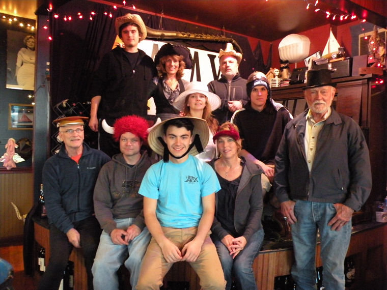 Employees at Ajax picked out their favorite hats for a quick photo on stage before getting busy serving customers. Pictured on bottom are (from left) Bill Davis, Jason Bates, Lewis Hagen, Debi Avery, Dee Neet. Pictured on top are (from left) Graham Welch, Kimberly Tornes, owner Kristan McCary, Dov Hayes and Mare Niccolson. Photo by Allison Arthur