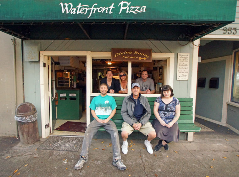 Waterfront Pizza employees (from left, front to back) Angelo Giangrosso, Mike Pruitt, Autumn Peterson, Jenn Pope, Mary Schultz and Paul Sale gather in the front window and bench of the restaurant's ground floor. Owner Diann Kuchera is not pictured. Photo by Nicholas Johnson