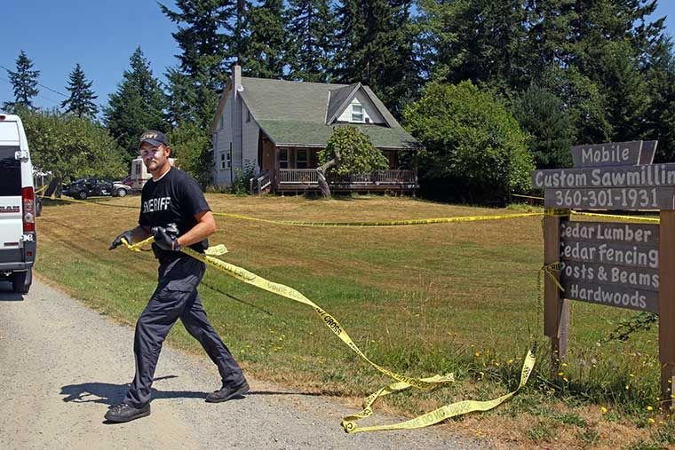 Jefferson County Sheriff's Office detective Ryan Menday handles crime scene tape as a Washington State Patrol Crime response team van enters the property along Swansonville Road west of Port Ludlow Thursday, July 23 following an apparent murder and attempted suicide. Photo by Nicholas Johnson