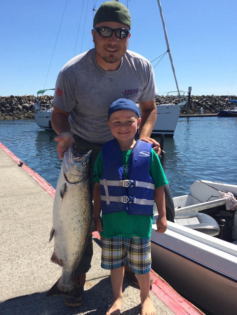 Jayden Minish with his father, Jason Minish, and the 16-pound, 5-ounce chinook salmon the Chimacum boy landed that won the children's salmon derby prize. Submitted photo