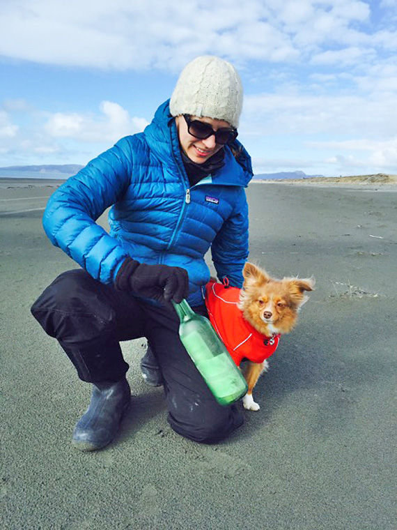 "Mikki Stazel, with her dog, Surly, shows off the bottle found April 4, 2015 on Okalee Spit east of Cordova along the Gulf of Alaska. Stazel and her boyfriend Kevin Easley have been collecting beach debris from the 2011 Japanese tsunami and are making a documentary, ""Lost and Found,"" but had never found a ""message in a bottle."" Photo by Kevin Easley"