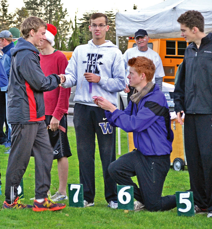 Sequim High's Peter Ohnstad went down on his knee to honor Port Townsend senior Ryan Clarke as the two-time Olympic League cross country champion went down the line of top finishers Oct. 23, 2014. Photo by Matthew Nash, Sequim Gazette