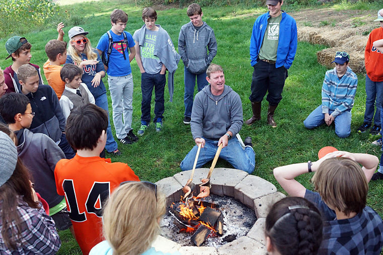 Aaron Stark, executive chef at Jefferson Healthcare, demonstrates a traditional method of roasting salmon over a fire Friday, Oct. 3 at Finnriver Farms with Blue Heron seventh-graders. Photo by Nicholas Johnson