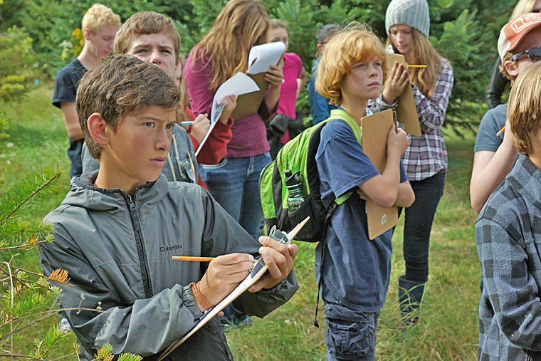 Seventh-grade students from Blue Heron School take notes while walking the land along Chimacum Creek at Finnriver Farm on Friday, Oct. 3. The students observed various types of trees and considered which might best combat reed canarygrass. Photo by Nicholas Johnson