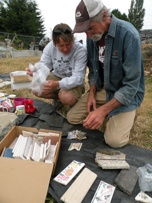 Shannon Burns of Port Townsend chats with Wayne Chimenti about items she brought to put on Al Nejmeh's memorial bench, which is in a garden behind Farm's Reach Café along State Route 19 in Chimacum. Photo by Allison Arthur