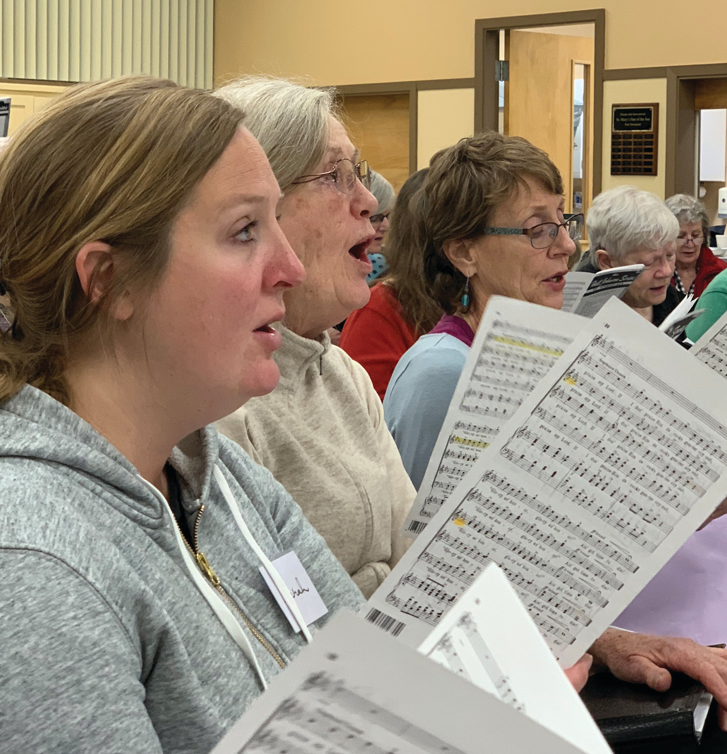 Choristers in the soprano section rehearse a spiritual.