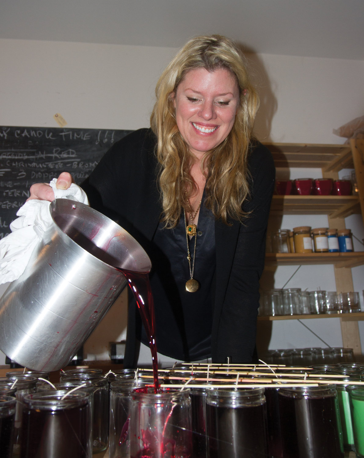 Heather Pollock Sehulster, owner of Conservatory Coastal Home, pours scented liquid wax into glass jars in the back room of her shop. The candles are popular as gifts among customers, she said.