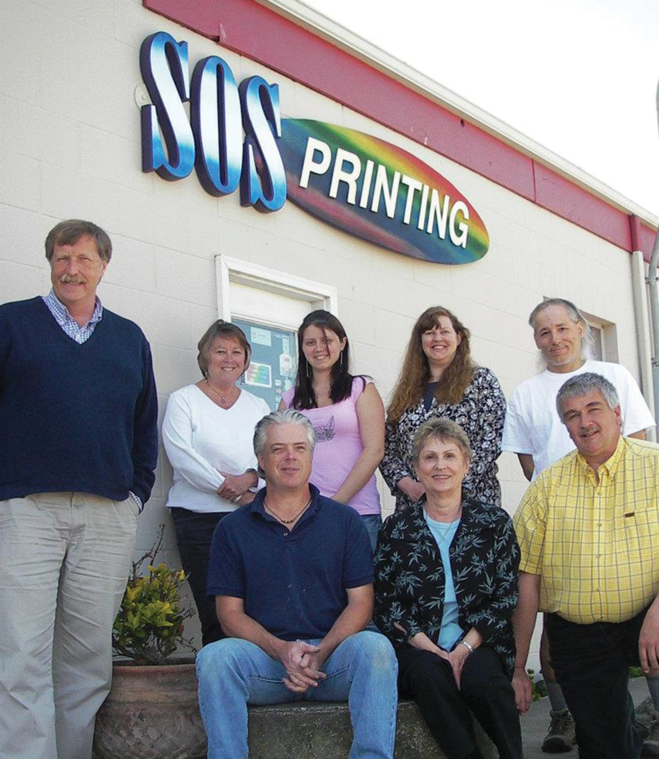 Dan Huntingford, left, with staff members Virginia, Desi, Debbie, Ron, Kim, Jan and Randy, outside of SOS Printing in 2012.