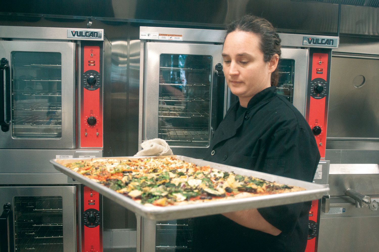 Shannon Minnihan, lead cook at Salish Coast Elementary, prepares to serve up trays of pizza to her students.