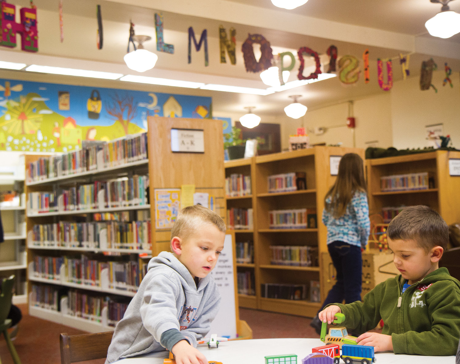 Hudson, left, and Emmett Douglas enjoy the children's library, which is freshly decorated by the Surface Design Association, which created the 26 letters of the alphabet in fiber and paper art.