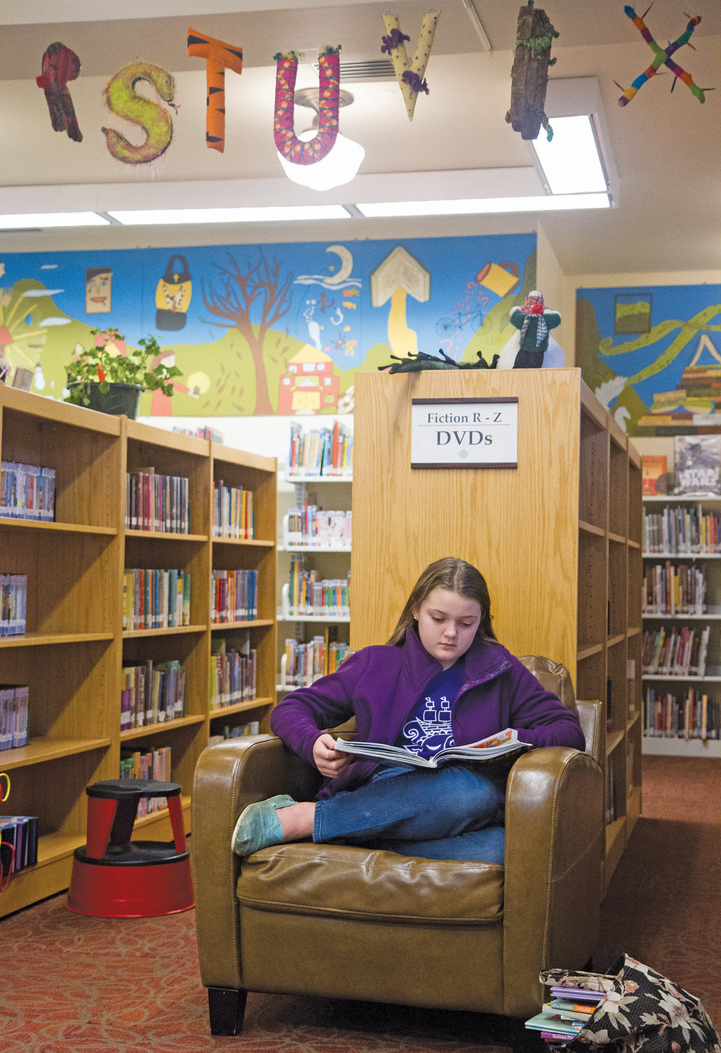 Sierra Douglas sits beneath the Port Townsend Library's new alphabet letters, immersed in a book.